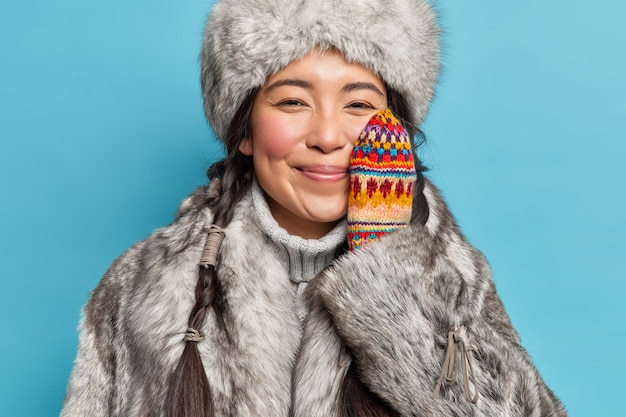 Wesoła, delikatna eskimoska w zimowych ubraniach trzyma rękę na policzku cieszy się zimą, radośnie pozuje na tle niebieskiej ściany. zimny klimat
