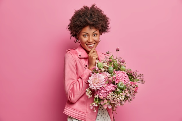 Wesoła, delikatna, młoda afroamerykańska kobieta w dobrym nastroju, dostaje śliczne kwiaty, cieszy się fajnym prezentem, szeroko się uśmiecha, pozuje w domu. zadowolony nauczyciel otrzymuje bukiet od uczniów w dniu wiedzy