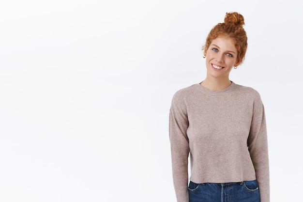 Wesoła, delikatna, przystojna rudowłosa kaukaska kobieta z uczesaną kędzierzawą fryzurą, nosi sweter, przechyla głowę i przyjemnie się uśmiecha, stoi swobodnie, wyraża pozytywną atmosferę, stoi biała ściana