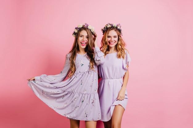 Wesoła długowłosa kobieta bawi się swoją fioletową sukienką podczas pozowania z przyjacielem