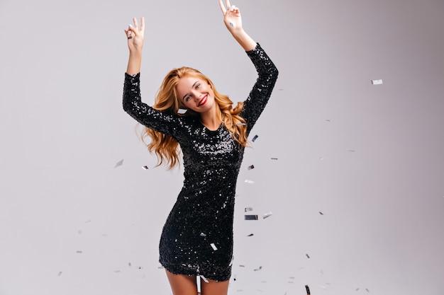 Wesoła, dobrze ubrana kobieta tańczy na imprezie. ładna elegancka dziewczyna w czarnej sukience pozuje pod błyszczącym konfetti.