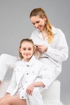 Wesoła, dobrze wyglądająca długowłosa kobieta siedząca za swoją młodszą siostrą i robiąca jej niezwykłą fryzurę