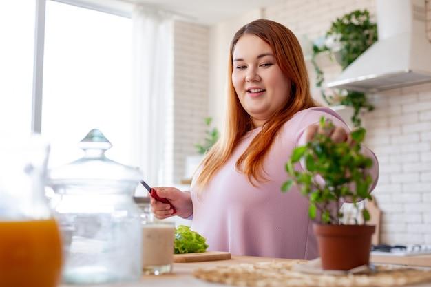 Wesoła, dobrze wyglądająca kobieta uśmiechająca się podczas gotowania w kuchni