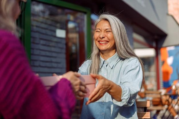 Wesoła dojrzała azjatycka kobieta z przyjacielem trzyma pudełko siedzące przy małym stoliku w kawiarni