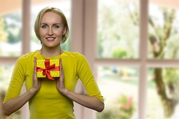 Wesoła dojrzała kobieta trzyma małe żółte pudełko upominkowe