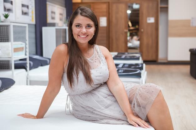 Wesoła dojrzała krągła kobieta uśmiechnięta, siedząca na łóżku ortopedycznym w sklepie meblowym