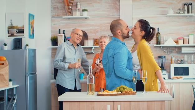 Wesoła dojrzała para przytula się i flirtuje w kuchni przed starszymi rodzicami, pijąc białe wino. młoda rodzina romantyczna, zabawna, mająca czułość i czułość w nowoczesnej, luksusowej jadalni