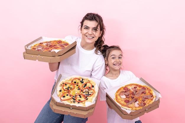 Wesoła dorosła dziewczyna i jej młodsza siostra z pizzą w pudełkach do dostawy na różowym tle.