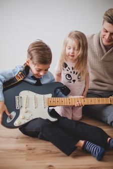 Wesoła dziecko gra na gitarze jego ojca