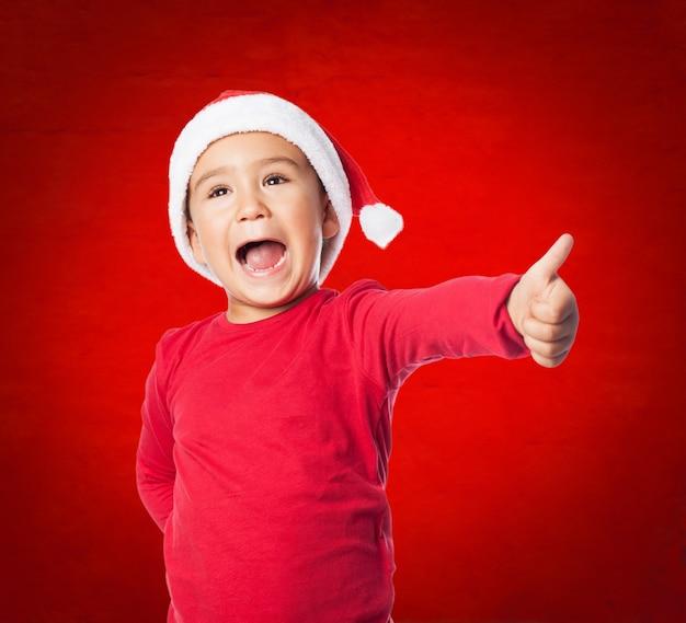 Wesoła dziecko robi gest zwycięstwa