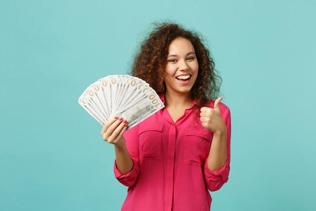 Wesoła dziewczyna afryki pokazuje kciuk w górę, trzymając wentylator pieniędzy w banknotach dolara, pieniądze w gotówce na białym tle na tle niebieskiej ściany turkus. ludzie szczere emocje, koncepcja stylu życia. makieta miejsca na kopię.