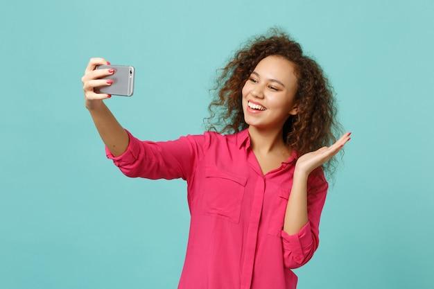Wesoła dziewczyna afryki w różowe ubrania dorywczo robi selfie strzał na telefon komórkowy na białym tle na tle niebieskiej ściany turkus w studio. ludzie szczere emocje, koncepcja stylu życia. makieta miejsca na kopię.