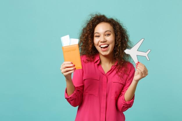 Wesoła dziewczyna afryki w ubranie posiadające paszport przepustkę pokładową bilet, papierowy samolot na białym tle na tle niebieskiej ściany turkus. koncepcja życia szczere emocje ludzi. makieta miejsca na kopię.