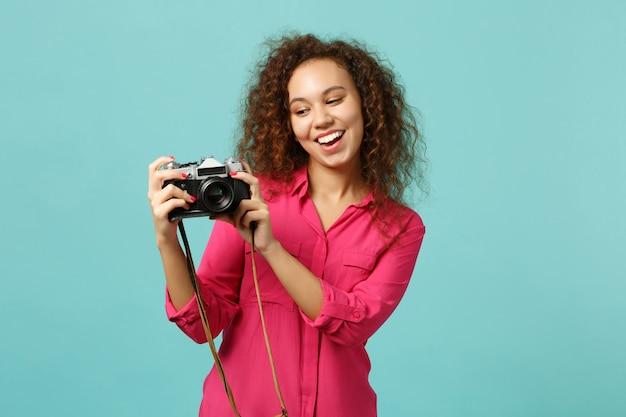 Wesoła dziewczyna afryki w ubranie robienia zdjęć na aparat retro vintage zdjęcie na białym tle na tle niebieskiej ściany turkus w studio. koncepcja życia szczere emocje ludzi. makieta miejsca na kopię.