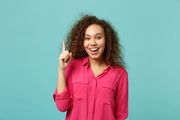 Wesoła dziewczyna afryki w ubranie trzyma palec wskazujący z nowym świetnym pomysłem na białym tle na tle niebieskiej ściany turkus w studio. koncepcja życia szczere emocje ludzi. makieta miejsca na kopię.