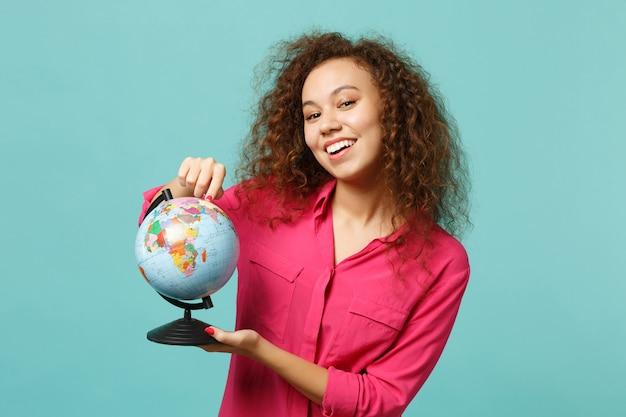 Wesoła dziewczyna afryki w ubranie wskazując palcem wskazującym na kuli ziemskiej ziemi na białym tle na tle niebieskiej ściany turkus w studio. ludzie szczere emocje, koncepcja stylu życia. makieta miejsca na kopię.