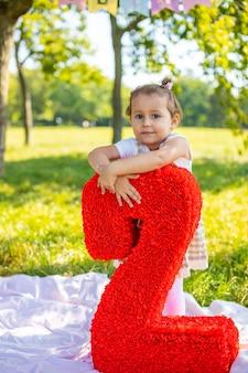 Wesoła dziewczyna bawi się na urodziny dziecka na kocu z papierowymi dekoracjami w parku