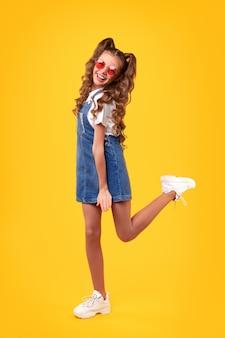 Wesoła dziewczyna całego ciała z warkoczykami w modnych okularach przeciwsłonecznych, ubrana w swobodną dżinsową sukienkę i trampki, bawiąca się