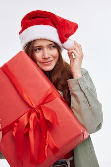 Wesoła dziewczyna czerwone pudełko santa hat przycięty widok jasnym tle. wysokiej jakości zdjęcie
