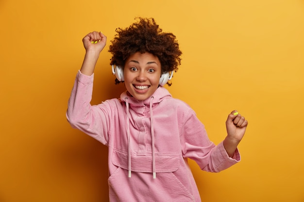 Wesoła dziewczyna dobrze się bawi, słucha muzyki, relaksuje się przy ulubionym utworze, nosi słuchawki bezprzewodowe, tańczy z podniesionymi rękami, nosi aksamitną bluzę z kapturem odizolowaną od żółtej ściany. świetna piosenka poprawia nastrój