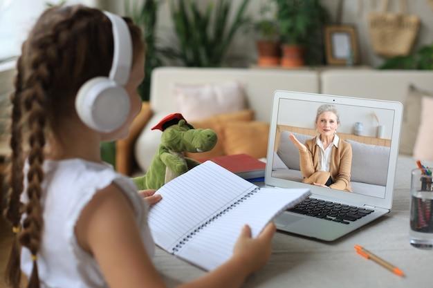 Wesoła dziewczyna dziewczyna w słuchawkach za pomocą laptopa, studiując przez system e-learningu online
