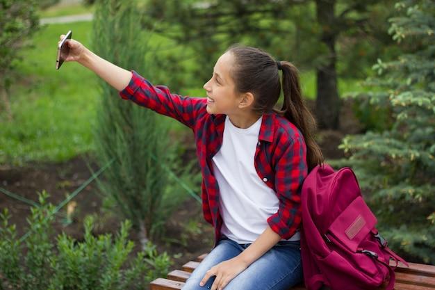 Wesoła dziewczyna entuzjastycznie używa telefonu do komunikacji w komunikatorze i robi sobie selfie