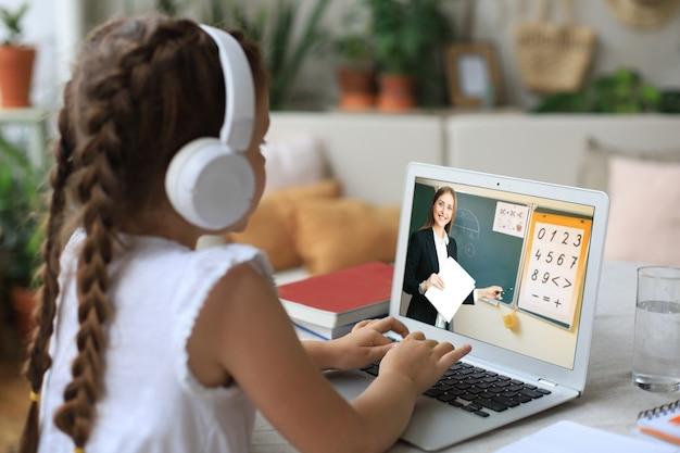Wesoła dziewczyna korzystająca z laptopa, ucząca się przez system e-learningu online
