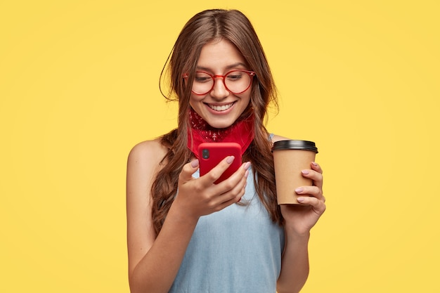 Wesoła dziewczyna ma przerwę na kawę, cieszy się z zakupu nowego gadżetu, czyta powiadomienie na czerwonym telefonie komórkowym, aktualizuje ulubioną aplikację, wpisuje wiadomość i uśmiecha się na ekranie, nosi okulary, odizolowana na żółtej ścianie