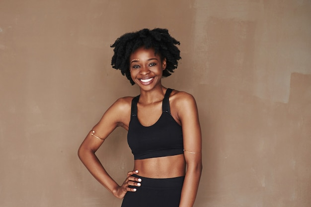 Wesoła dziewczyna. młoda piękna kobieta afro american przeciwko brązowej przestrzeni