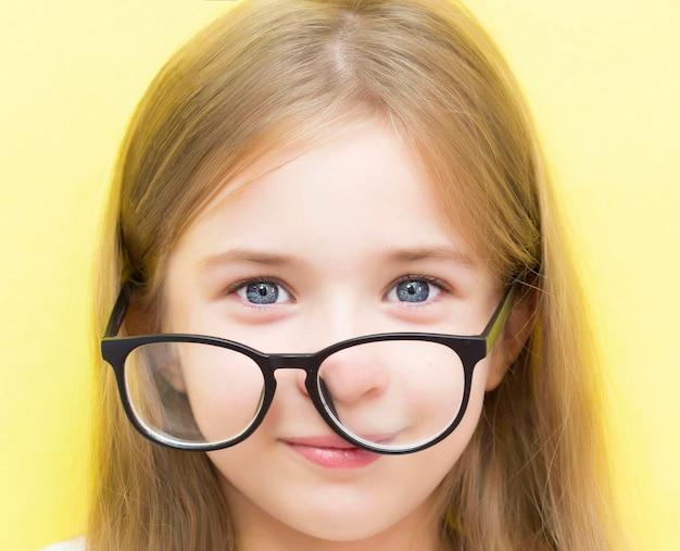 Wesoła dziewczyna na żółtym tle w okularach i trzymająca soczewki kontaktowe. pojęcie problemów ze wzrokiem u dzieci w wieku szkolnym.