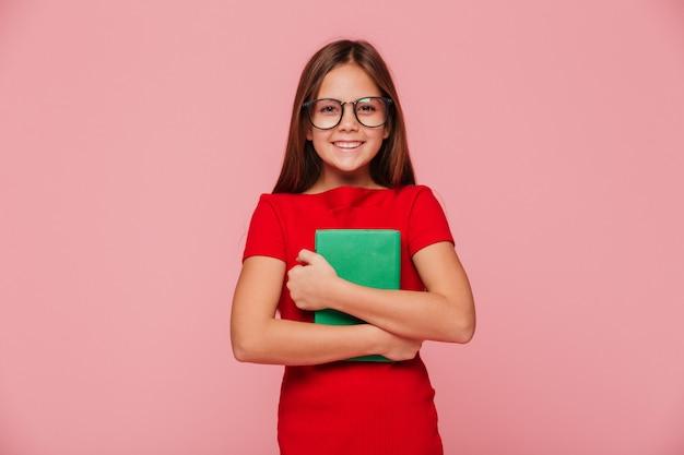 Wesoła dziewczyna nerd gospodarstwa książki i patrząc
