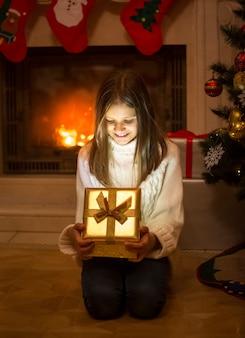 Wesoła dziewczyna otwierając pudełko z prezentem świątecznym. lekkie i lśniące iskierki wychodzące z pudełka