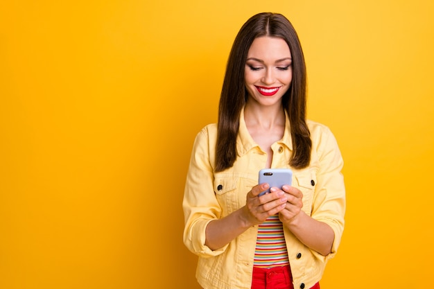Wesoła dziewczyna patrząc na telefon z zębatym uśmiechem w pobliżu pustej przestrzeni na białym tle żywy kolor ściany