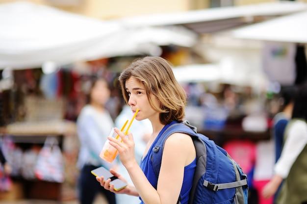 Wesoła dziewczyna pije sok na ulicy rzymu