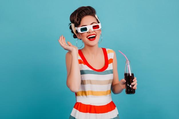 Wesoła dziewczyna pinup pozuje w okularach 3d. studio strzał błogi brunetka kobieta z butelką sody na białym tle na niebieskim tle.