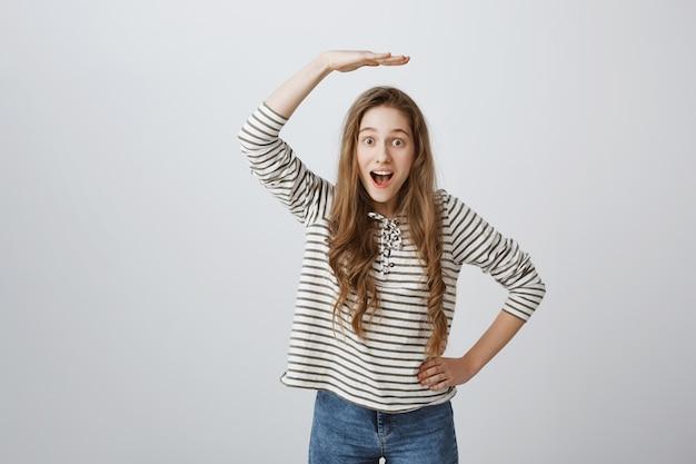 Wesoła dziewczyna podnosząca rękę nad głowę i wyglądająca na zdumioną, pokazująca wzrost