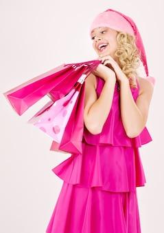 Wesoła dziewczyna pomocnika santa z torby na zakupy