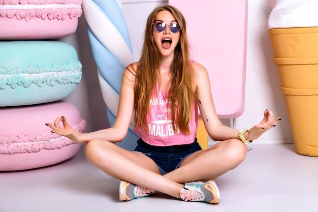 Wesoła dziewczyna śmieszne siedzi na podłodze w pozycji lotosu. szczęśliwa blondynka w różowy podkoszulek i spodenki, uśmiechając się i robiąc grymas twarzy. medytacja i szalone emocje, przyjemność