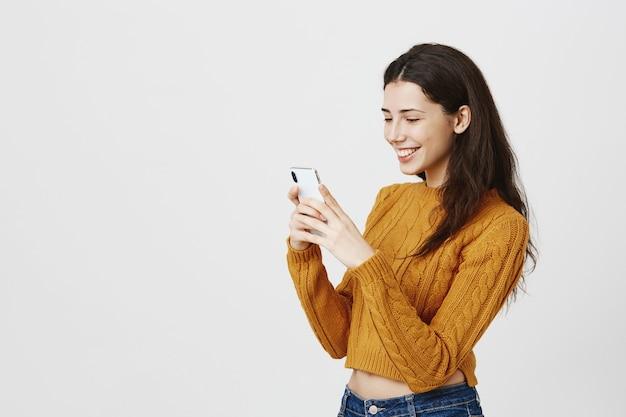Wesoła dziewczyna sms-y w aplikacji randkowej, patrząc na smartfona z radosnym uśmiechem