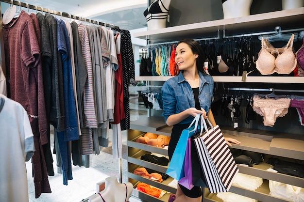 Wesoła dziewczyna spaceru w sklepie odzieżowym