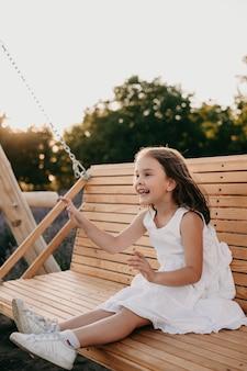 Wesoła dziewczyna ubrana w białą sukienkę siedzi na huśtawce, bawiąc się w letni wieczór