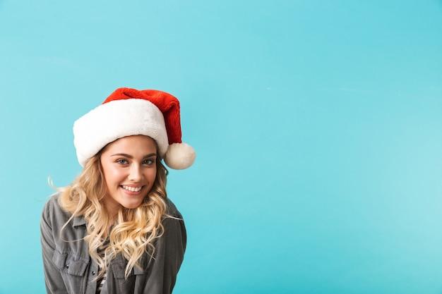 Wesoła dziewczyna ubrana w boże narodzenie kapelusz stojący na białym tle nad niebieskim
