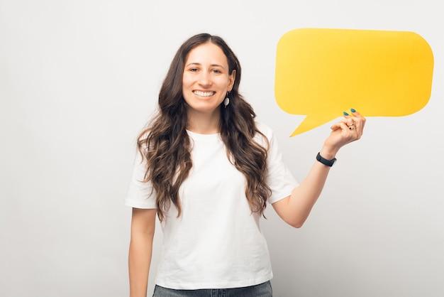 Wesoła dziewczyna uśmiecha się do kamery trzyma żółty dymek.