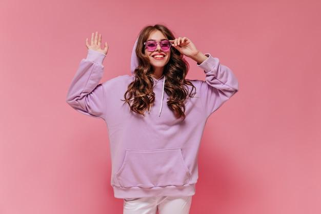 Wesoła dziewczyna w białych spodniach i fioletowej bluzie z kapturem zdejmuje okulary przeciwsłoneczne i szeroko się uśmiecha