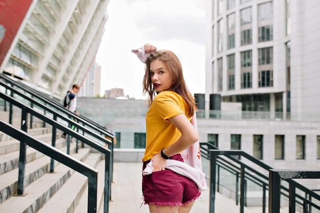 Wesoła dziewczyna w jasnym stroju patrząc przez ramię z zainteresowaniem spacerując po miejskiej ulicy