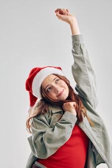 Wesoła dziewczyna w kapeluszu świętego mikołaja podniosła rękę na jasnym tle. wysokiej jakości zdjęcie
