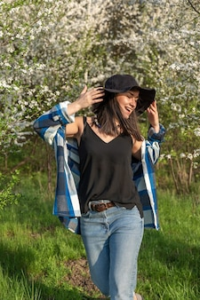 Wesoła dziewczyna w kapeluszu wśród kwitnących drzew na wiosnę, w stylu casual