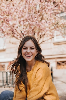 Wesoła dziewczyna w kaszmirowym swetrze śmieje się na tle kwitnącej sakury. portret kobiety w żółtej bluzie z kapturem w mieście na wiosnę
