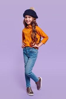 Wesoła dziewczyna w modnym casualowym stroju i berecie