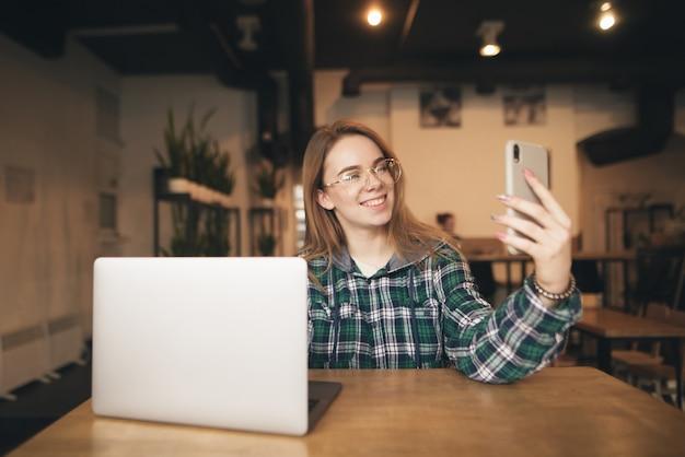 Wesoła dziewczyna w okularach i luźnej sukience siedzi w kawiarni z laptopem, robi selfie na smartfonie, uśmiechając się i pozując